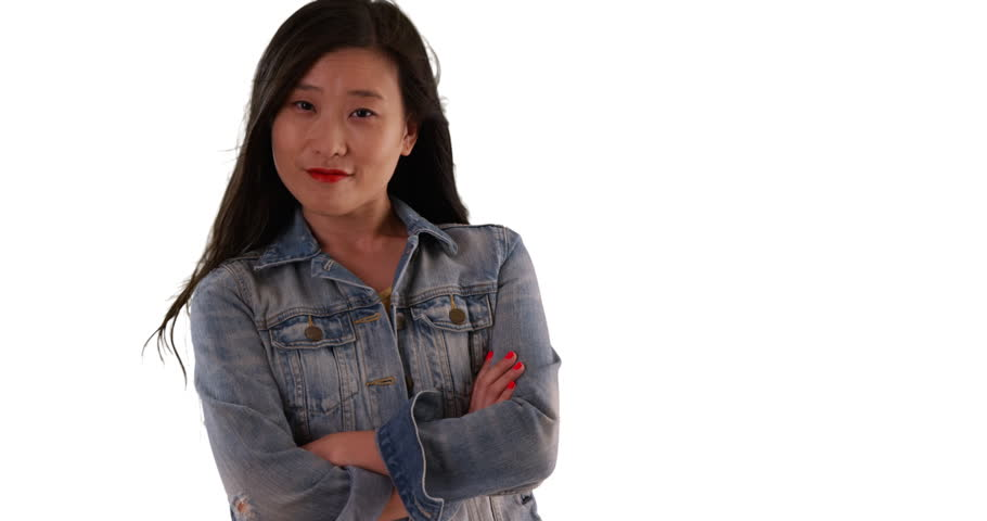 Chinese woman in denim jacket with arms crossed on a solid white backdrop smiles at camera. Asian millennial in her 20s with hair blowing in the wind. 4k
