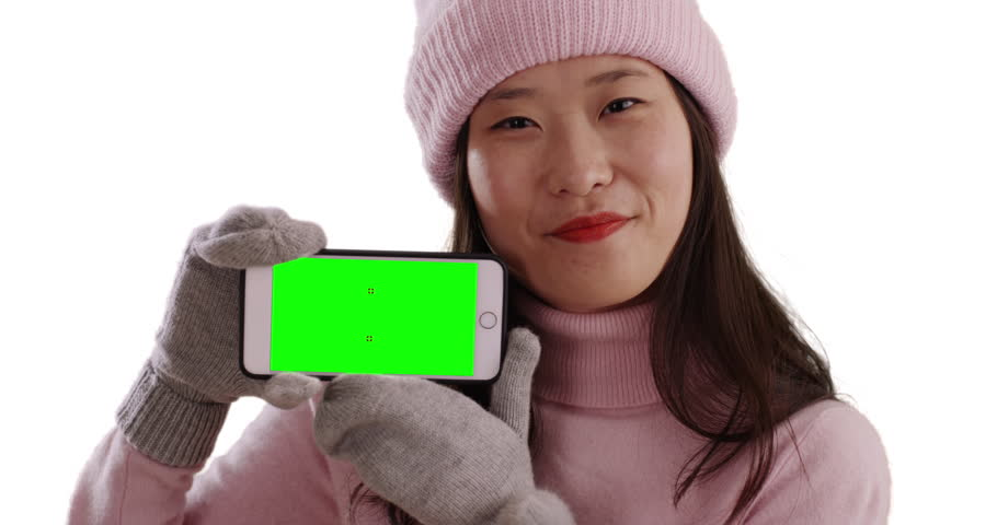 Smiling Asian woman in winter clothing holding smartphone with green screen on white background. Happy millennial with gloves and sweater holds up cell phone to share screen with copy space. 4k | Shutterstock HD Video #1009888013