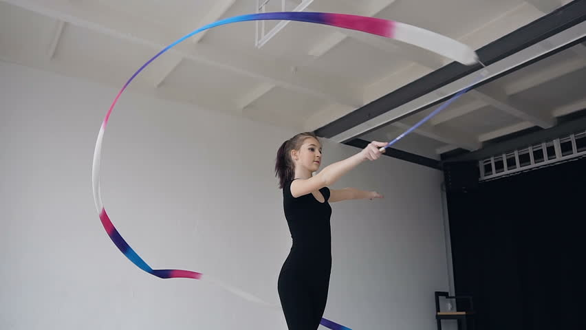 Attractive female gymnast dancing with colored ribbon in gymnastics school. Slim gymnast in black body performs the gymnastics exercise with a ribbon in the white studio and possing to the camera | Shutterstock HD Video #1009888733
