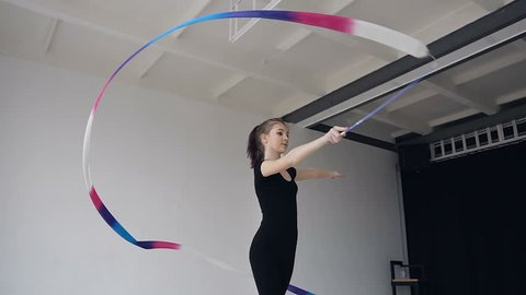 Attractive female gymnast dancing with colored ribbon in gymnastics school. Slim gymnast in black body performs the gymnastics exercise with a ribbon in the white studio and possing to the camera