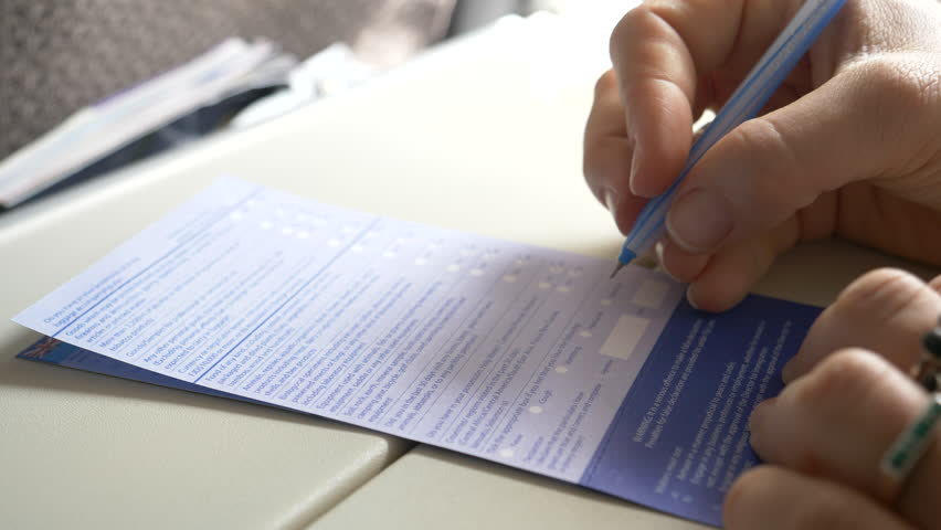 CLOSE UP, DOF: Unknown businesswoman signs an important immigration form during her flight to the United States. Young Caucasian woman signs and fills out a mandatory background check questionnaire.