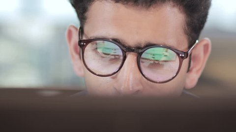 close up of a young and busy businessman wearing eyeglasses working on computer. Reflection of computer screen can be seen in the eyeglasses of an handsome male entrepreneur in modern corporate office