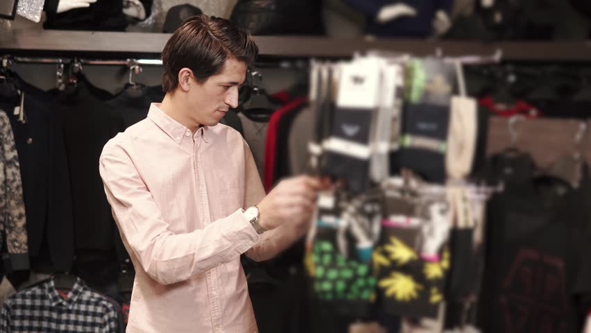 A young man examines the stand with socks, he needs to buy a gift for the clothes for the feet, the person carefully studies the composition and looks at the design on his socks   Shutterstock HD Video #1009976273