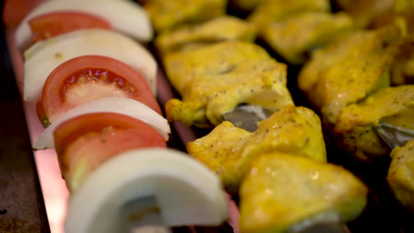 Closeup of saffron soaked chicken kabobs and tomato and onion kabobs on a grill.