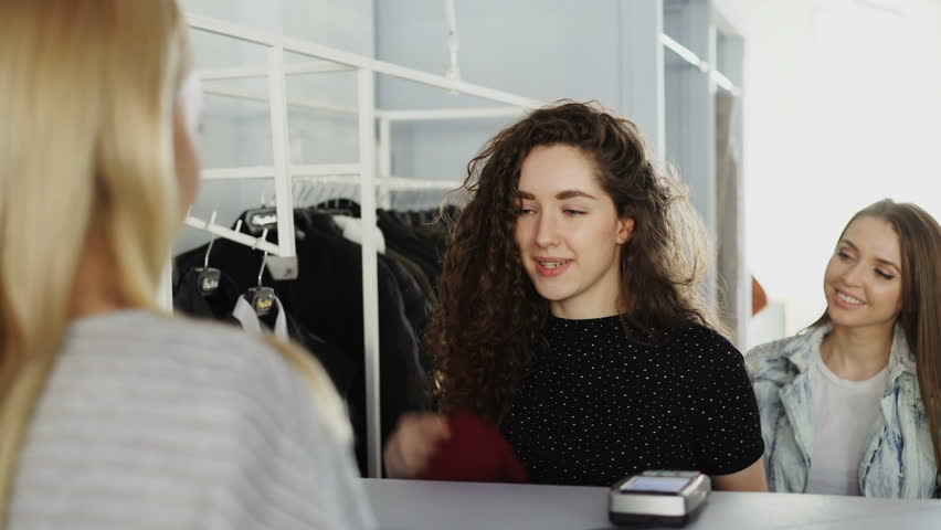 Close-up shot of female customers paying for clothes at cashier's desk in clothing boutique. Young woman is making payment with smart phone, taking bag with purchases and going out | Shutterstock HD Video #1009985663
