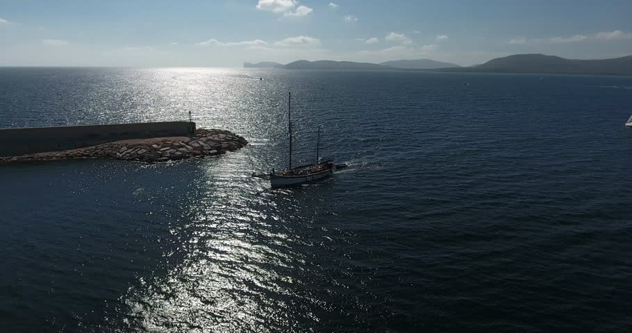 ALGHERO, SARDINIA, ITALY – JULY 2016 : Aerial shot of sailboat arriving to Alghero harbor on a sunny day with cityscape and sea in view