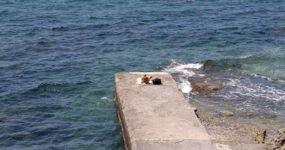 ALGHERO, SARDINIA, ITALY – JULY 2016 : Video shot of man sunbathing on Alghero beach on a sunny day