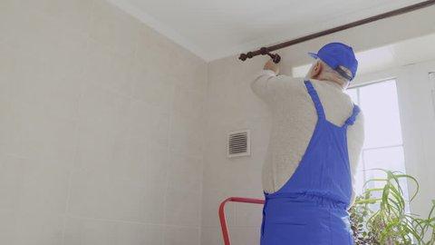 Mature man repair cornice for curtains