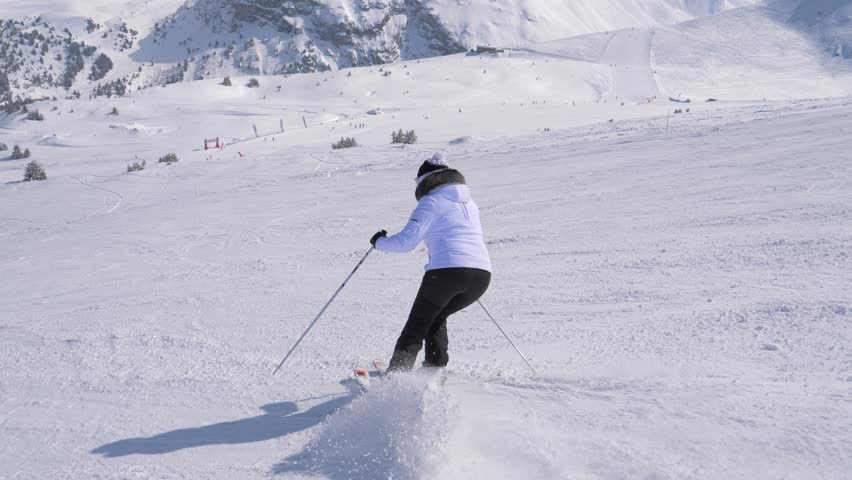 A woman in a white jacket and black trousers skis down on the slope alone. She turns left and right professionally with the help of ski sticks. Snowy high mountains are in the background, slow motion | Shutterstock HD Video #1009994303