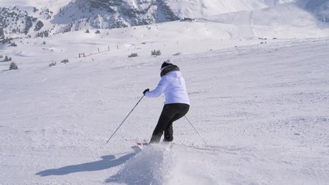 A woman in a white jacket and black trousers skis down on the slope alone. She turns left and right professionally with the help of ski sticks. Snowy high mountains are in the background, slow motion