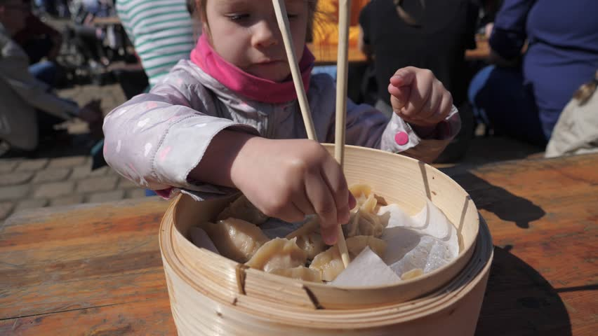 Child girl eating chewing asian dumpling with chopsticks at street food festival