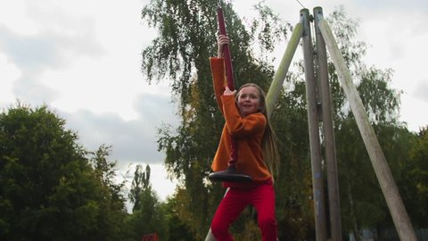 Little Girl Riding on a Zipwire in an adventure playground - super slow motion