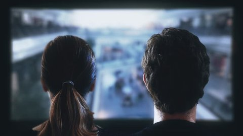 Watching Movies In Theater. Couple watching a movie in a theater. Shot behind model shoulders.