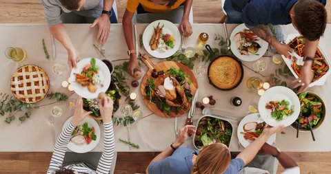 top view of young cheerful multi ethnic friends preparing table enjoying vibrant thanksgiving lunch together talking bonding over healthy meal time lapse