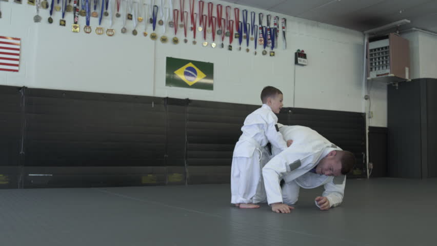 Instructor practicing Jiu-jitsu moves with a boy