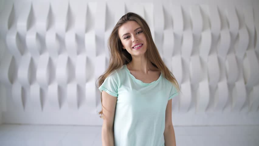 Attractive young woman wearing a light green t shirt is smiling and flirting while standing against a white geometric pattern wall. Handheld real time medium shot   Shutterstock HD Video #1010016713