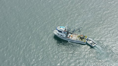 Alaska - September, 2017: Aerial overhead ocean view of crew on small commercial fishing boat trawling of Baranof Island near Sitka Southeast America