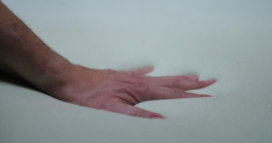 A hand slowly presses into a soft foam mattress.