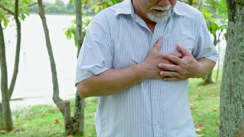 Senior man having a heart attack. Chinese old man is having chest pain. Outdoor in park.
