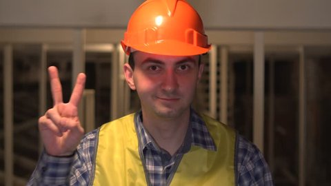 Gesture of Success, Victory Sign by Worker or an Engineer or architect on construction site. Concept: construction, worker, engineering, design Victory.