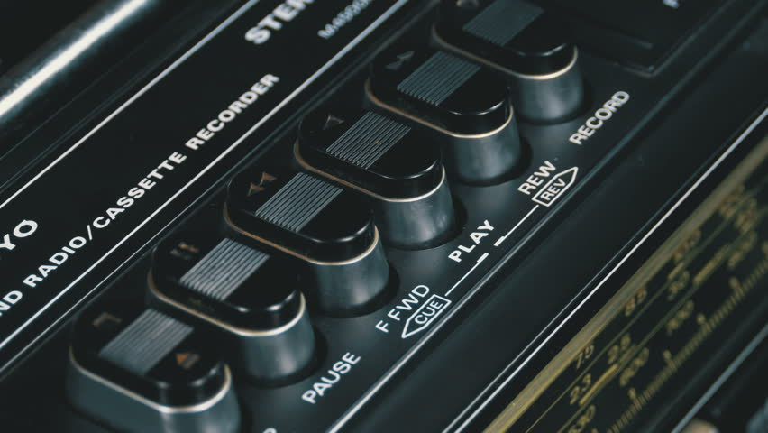 Pushing Button on a Tape Recorder, Play, Stop, Rec, ff, Rew. Close-up. Man finger presses playback control buttons on vintage audio cassette player.   Shutterstock HD Video #1010096483