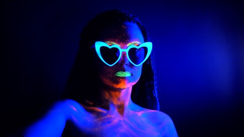 Fashion sexy dancer with heart shaped glasses in neon light. Fluorescent makeup glowing under ultraviolet light. Night club, party, psychedelic concepts. Mysterious woman with UV painting