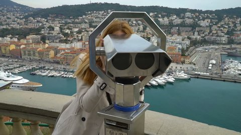 Traveler woman watching through the stationary binoculars at a scenic overlook in Nice, France