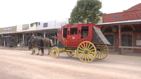 TOMBSTONE, ARIZONA/USA - NOVEMBER 07, 2017: Stagecoach goes down street in Tombstone, tracking shot. Tombstone is a historic city founded in 1879, one of the last boomtowns in the American frontier.