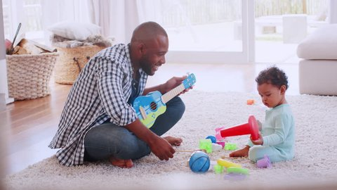 Young black father palying ukulele with son in sitting room
