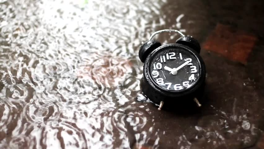 lonely alone classic black vantage alarm clock under rain in water