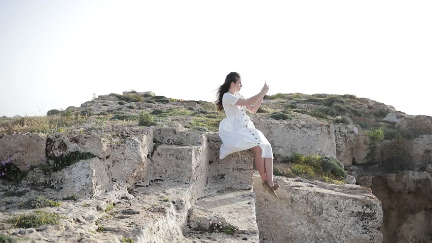 Young girl does photo near to the blue sea sitting on a mountain Woman Watching Sunset. Takes Panorama Photos On Phone. Hair in the Wind | Shutterstock HD Video #1010172173