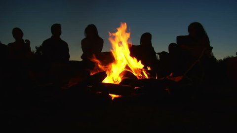 Silhouettes of people sitting around campfire
