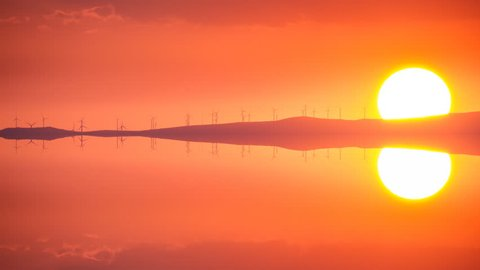 Time lapse of sunset over mountain range with clean energy Wind turbines reflection