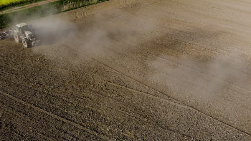 Aerial of tractor on field in dust (top view from height)  | Shutterstock HD Video #1010261693