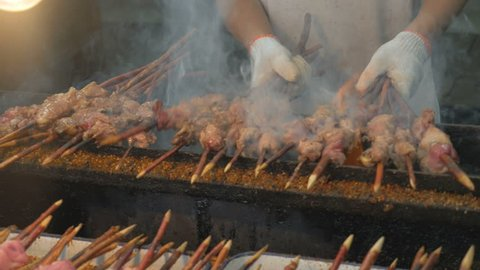 Close up, chef cooking skewers on grill, Beijing, China