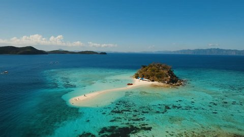 Aerial view of tropical beach on the Bulog Dos Island, Philippines. Beautiful tropical island with sand beach, palm trees. Tropical landscape: beach with palm trees. Seascape: Ocean, sky, sea. 4K