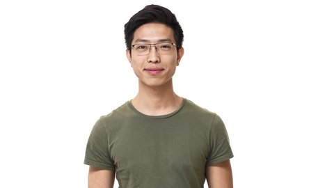 Portrait of pleased asian man wearing eyeglasses and basic t-shirt grinning with bright smile, isolated over white background. Concept of emotions