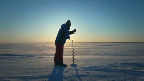 Fisherman drilling hole in ice lake for winter fishing on skyline background