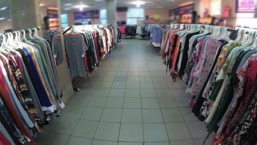 Rows with clothes on hangers hang in the second hand shop. View inside the shopping center. Second-hand clothes. | Shutterstock HD Video #1010289563