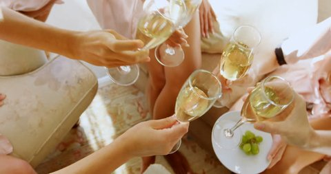Bridesmaids in nightdress toasting a glass of champagne at home 4K 4k