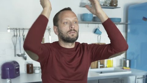 Upset man reading bills with bad news in kitchen