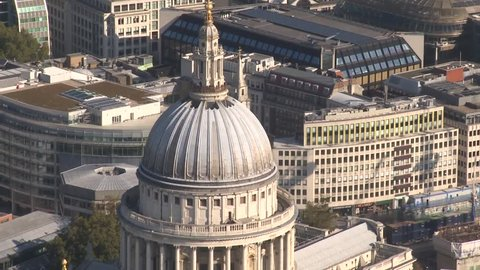 A wide aerial shot travelling over the top of St Paul's Cathedral dome on a sunny day in London. The footage shows the famous architecture close up. HD shot from a helicopter on a sunny day.