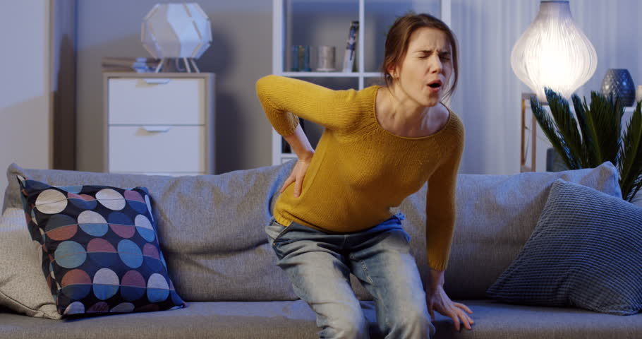 Young caucasian woman in the yellow sweater sitting on the gray couch in the living room late at night and holding her low back, feeling severe pain in it. Indoor