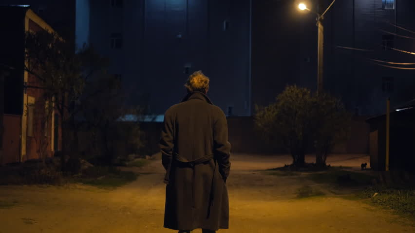 4k Man in coat walking at the danger night street of abandoned city with lamp light