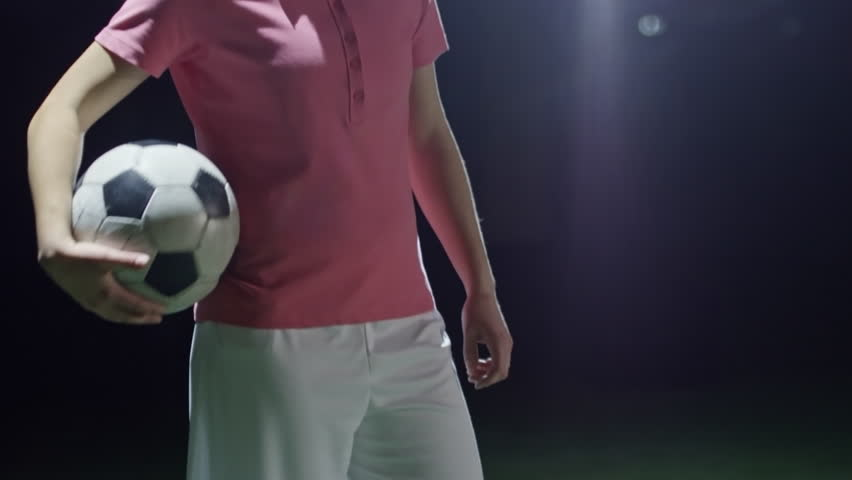Tilt up of female soccer player from junior league throwing a ball and running in dark sports arena | Shutterstock HD Video #1010318123