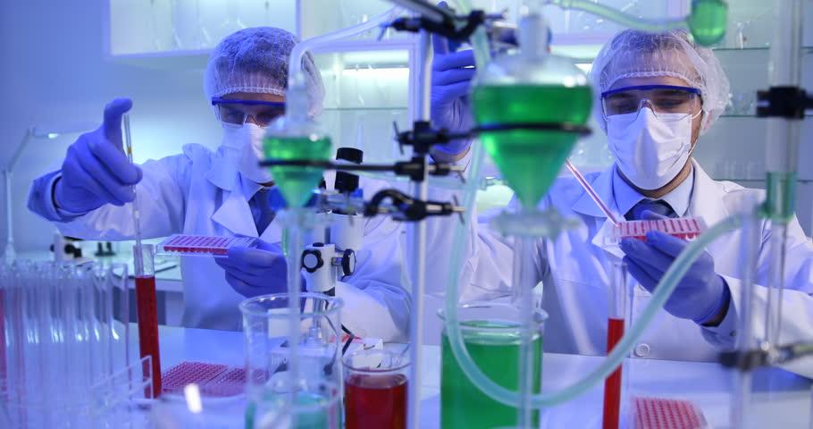 Biologist Researcher Men Using Micropipette Adding Test Liquid in Microplate Lab