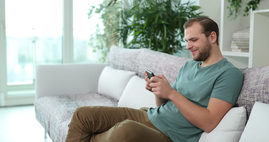 Attractive Man Play Games and Win on Mobile Phone Sitting on Sofa in Living Room