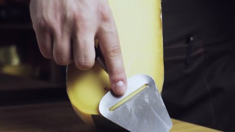Cheese sommelier in the store cuts a piece of cheese. Knife for cheese. Not a mature Gouda. Slow motion.