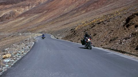 Spectacular scene with bikers riding motorcycles on Leh-Manali Highway flanked by rocky slopes of Himalaya mountains. Camera moves along road and passes by motorcyclists on bikes. Ladakh, India.