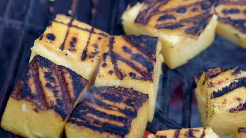 Extreme closeup of polenta smoking on a hot grill while the camera slides to the right.